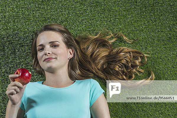 Porträt einer lächelnden Frau  die im Park auf Gras liegt und Apfel isst.