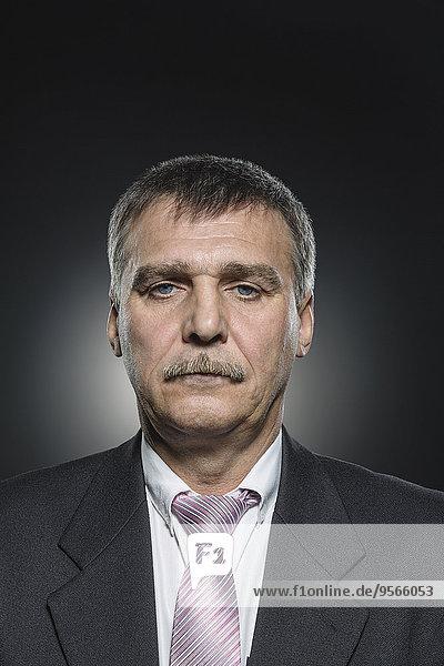 Porträt eines selbstbewussten Geschäftsmannes vor schwarzem Hintergrund