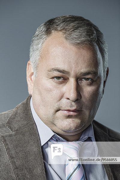 Porträt eines seriösen Geschäftsmannes vor grauem Hintergrund