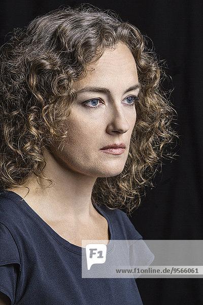 Nahaufnahme einer ernsthaften Frau vor schwarzem Hintergrund