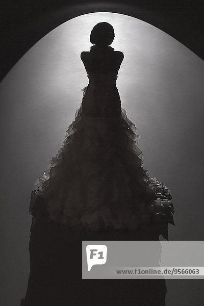 Rückansicht der punktbeleuchteten Braut vor schwarzem Hintergrund