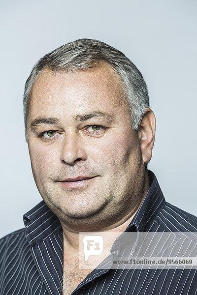 Porträt eines selbstbewussten Geschäftsmannes vor grauem Hintergrund