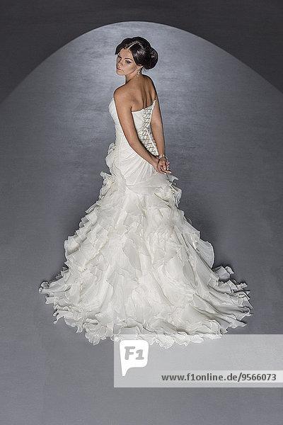 Hochwinklige Ansicht der punktbeleuchteten Braut vor grauem Hintergrund