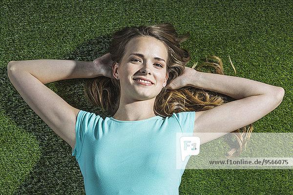 Hochwinkel-Porträt einer lächelnden Frau  die auf Gras im Park liegt.