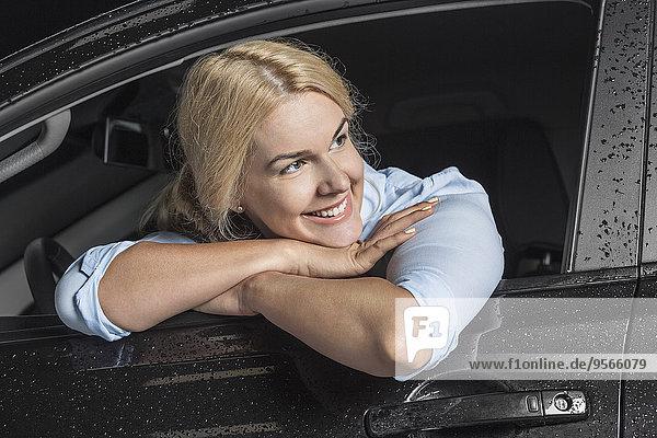Nahaufnahme einer glücklichen Frau  die wegguckt  während sie sich auf das Autofenster lehnt.