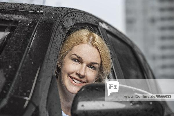 Porträt einer glücklichen Frau  die aus dem Autofenster schaut.