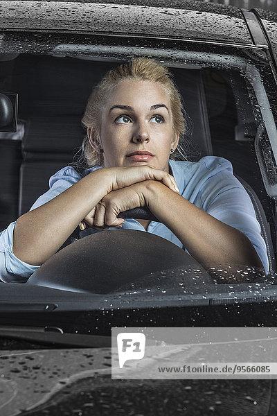 Nachdenkliche Frau entspannt am Lenkrad im Auto