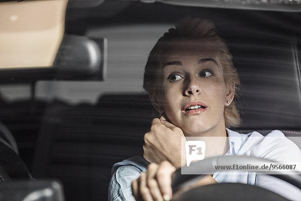 Mittlere erwachsene Frau im Rückspiegel beim Autofahren