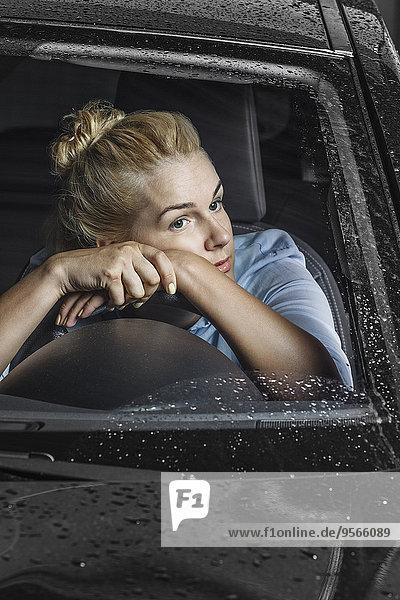 Gelangweilte Frau schaut weg  während sie sich im Auto auf das Lenkrad lehnt.