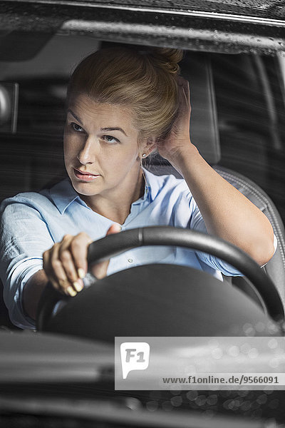 Mittlere erwachsene Frau  die sich selbst im Rückspiegel beim Autofahren ansieht