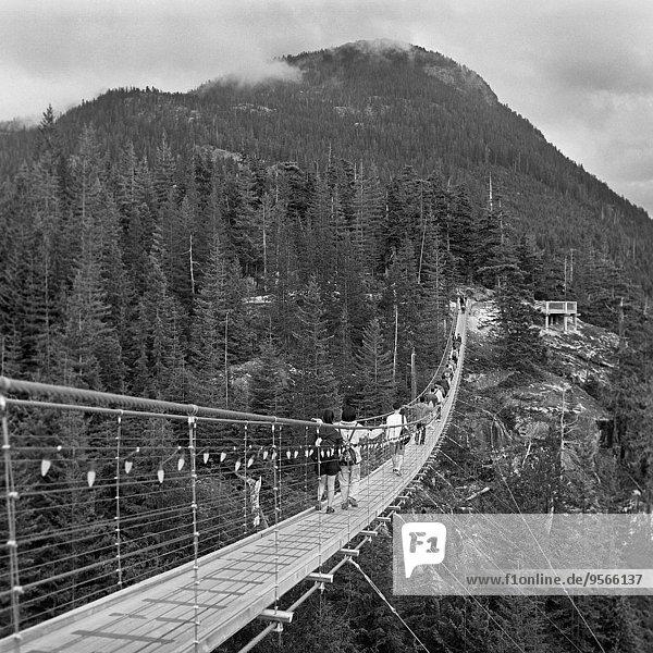 Menschen  die auf einer Fußgängerbrücke in Richtung Berg gehen. Menschen, die auf einer Fußgängerbrücke in Richtung Berg gehen.