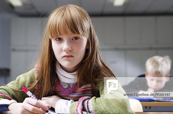 Ein Mädchen  das einen Stift in der Hand hält.