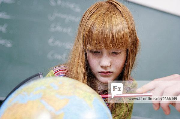 Eine Schülerin schaut mit ihrem Lehrer aufmerksam auf einen Globus.