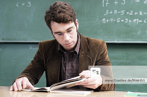 Ein Lehrer  der aufmerksam ein Buch liest.