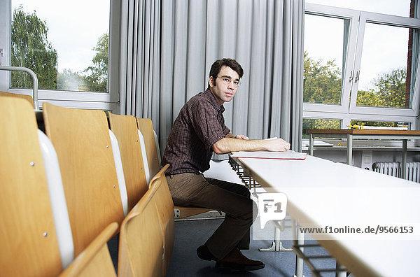 Ein Lehrer studiert seine Notizen in der Nähe eines Schulfensters.