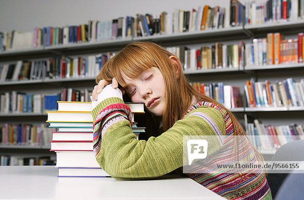 Ein Mädchen macht ein Nickerchen auf einem Stapel Bücher in einer Bibliothek.