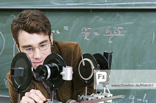 Ein Lehrer  der ein wissenschaftliches Instrument einstellt.