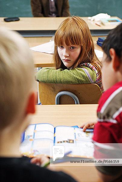 Ein Mädchen dreht sich um und starrt zwei Jungen in einem Klassenzimmer an.