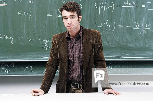 Ein Lehrer mit Physik-Gleichungen auf einer Tafel