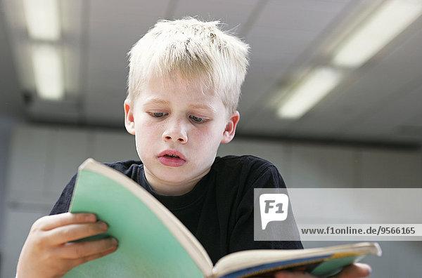 Vorderansicht eines kleinen Jungen beim aufmerksamen Lesen eines Buches