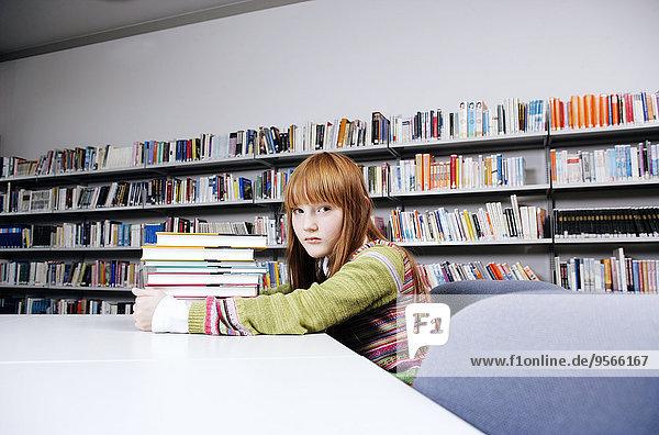 Ein Mädchen mit einem Haufen Bücher.