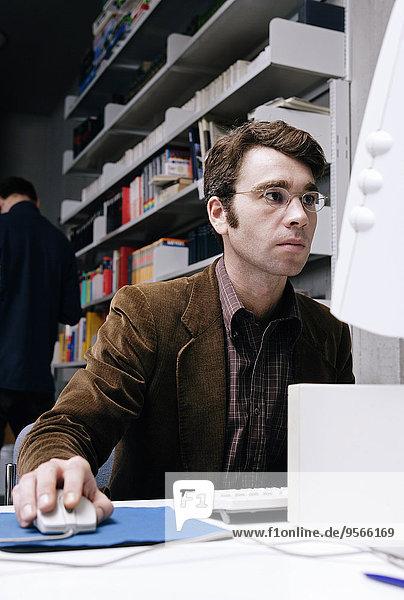 Ein Mann  der an einem Computer in einer Bibliothek arbeitet.