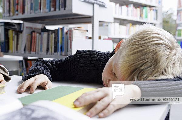Ein Junge macht ein Nickerchen auf einem Schreibtisch in einer Bibliothek.