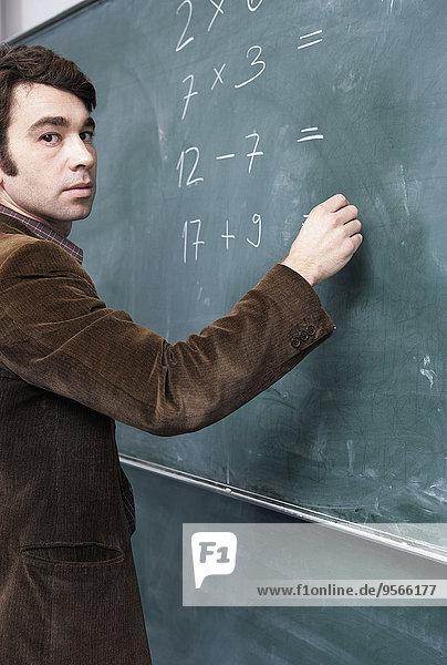 Seitenansicht eines Mannes  der auf einer Tafel schreibt