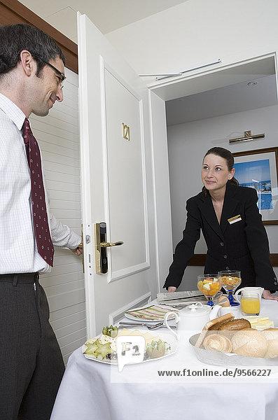 Frau liefert Frühstück auf Schiebewagen an Geschäftsmann im Hotelzimmer