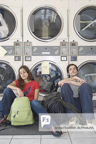 Junger Mann und junge Frau sitzen im Waschsalon