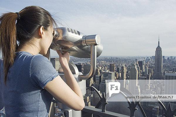 Junge Frau steht auf dem Dach des Gebäudes und schaut durchs Fernglas  New York City