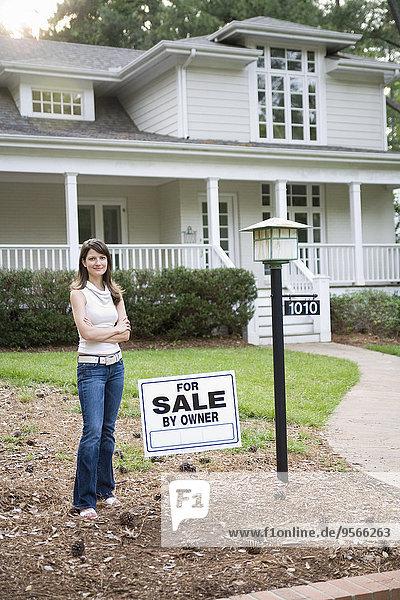 Eine junge Frau steht vor einem Haus zum Verkauf.
