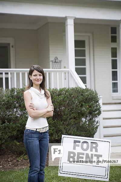 Eine junge Frau  die hinter einem zu vermieten -Schild steht.