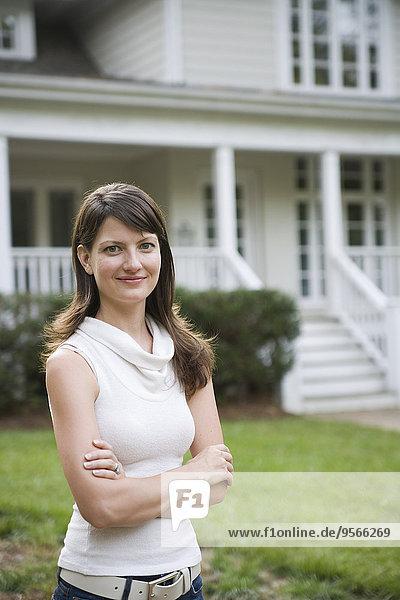 Eine junge Frau steht mit verschränkten Armen vor einem Haus.