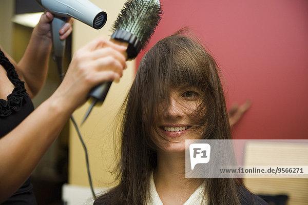 Ein Stylist fönt das Haar einer jungen Frau.