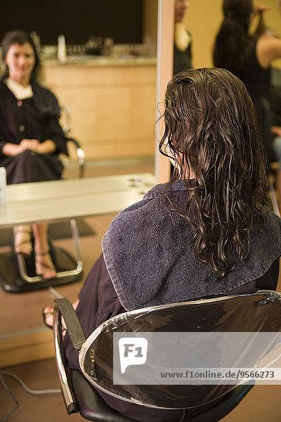 Eine junge Frau sitzt auf einem Stuhl in einem Salon.