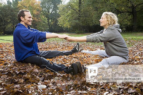 Mann und Frau sitzend und streckend auf Herbstlaub im Park