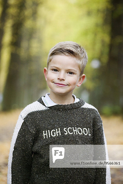 Young boy standing in park in autumn