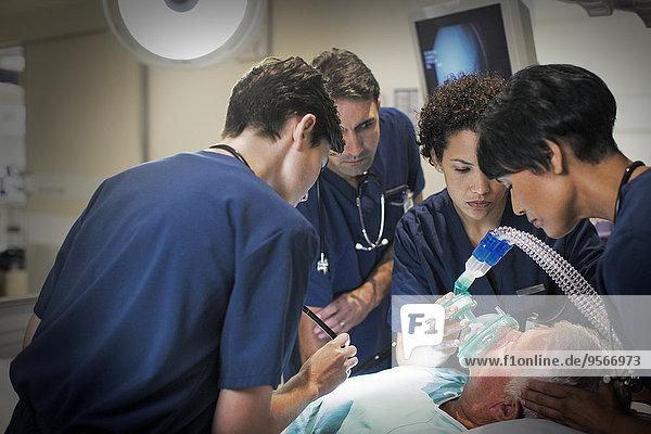 Ärztin mit Maske während der Betäubung älterer Patienten auf der Krankenstation
