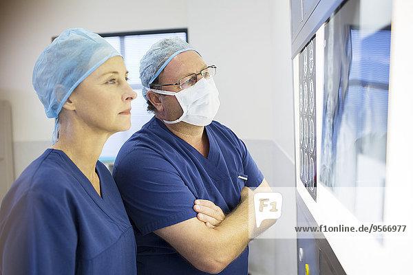 Zwei Ärzte besprechen vor der Operation das Röntgenbild und die Kernspintomographie des Patienten.
