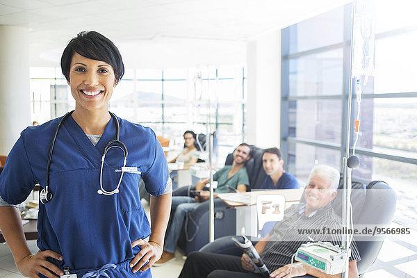 Porträt des Arztes mit Patienten  die im Hintergrund behandelt werden