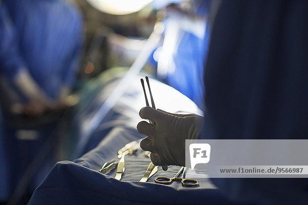Krankenschwester mit chirurgischem Werkzeug während der Operation