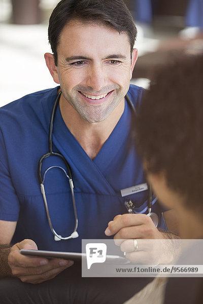 Porträt eines lächelnden Arztes mittlerer Größe mit einem Tablet PC