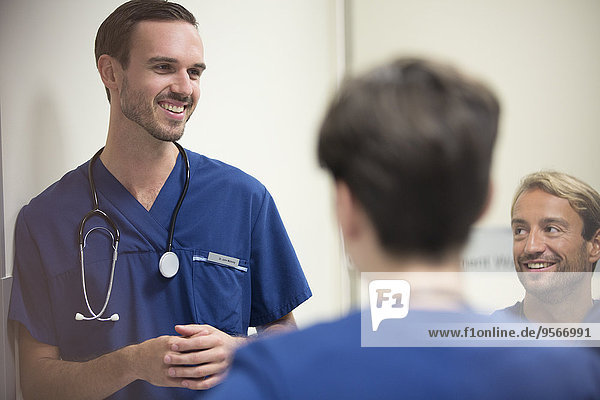 Ärzte lächeln und reden auf der Krankenstation