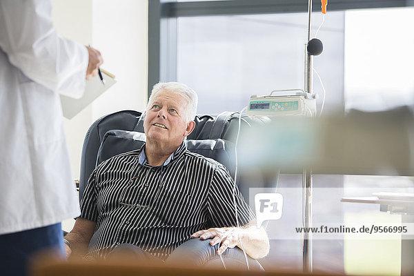 Arzt im Gespräch mit dem behandelten Patienten auf der Krankenstation