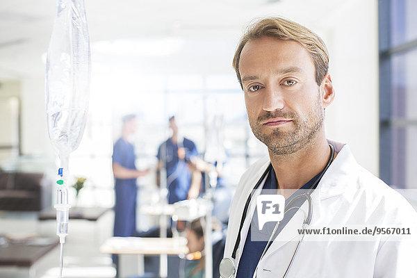 Porträt eines Arztes mittlerer Größe mit Kollegen im Hintergrund  stehend auf der Krankenstation