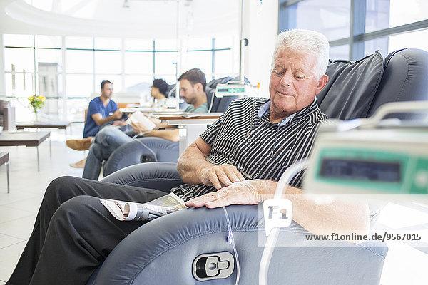 Seniorenpatient im Sitzen und Schauen auf der Krankenstation