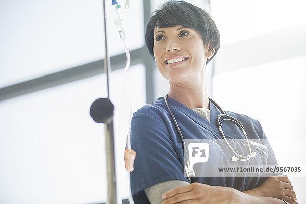 Porträt einer Ärztin vor dem Krankenhausfenster