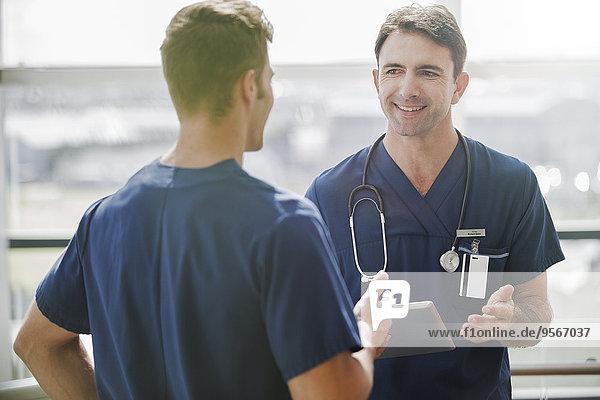 Zwei Ärzte im Gespräch  einer hält Tabletten-PC