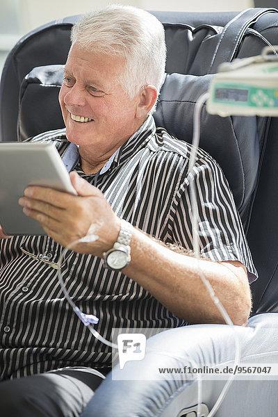 Senior Mann mit Tablette PC während der intravenösen Infusion